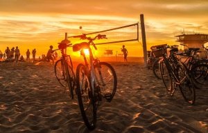 Bikes and volleyball on the beach at sunset